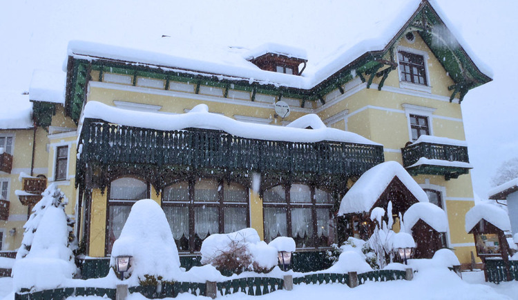 Here you can see the wintery exterior view of Hotel Goisererhof with its snow covered roof.