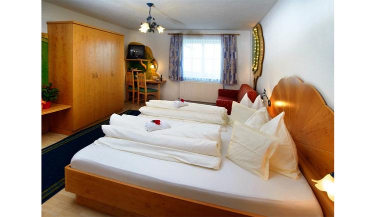 Schlafzimmer mit Doppelbett, im Hintergrund Couch, Fenster, Fernseher, seitlich ein Kleiderschrank