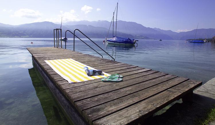 Steg am Attersee miit Handtuch und im Hintergrund Segelboote und Berge