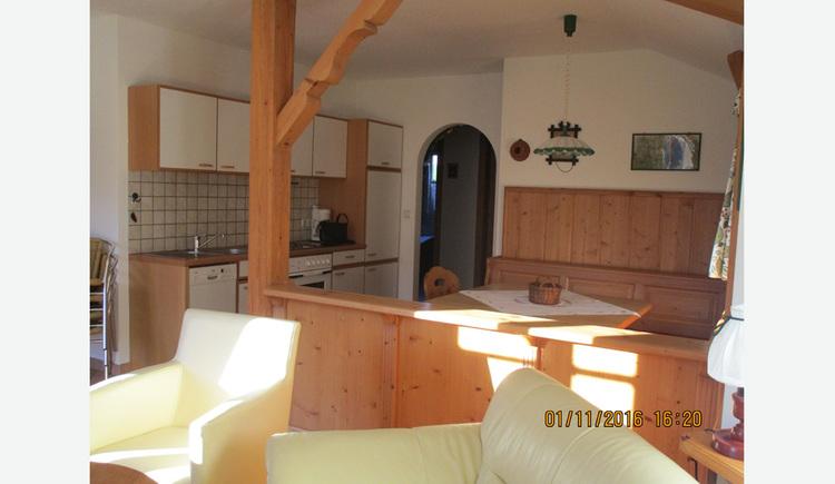 Wohnbereich: im Vordergrund ein Teil von der Couch, Stuhl, dahinter Essbereich mit Eckbank, Tisch und Stuhl, im Hintergrund seitlich, Küche mit Spüle, Geschirrspüler, Herd, Kaffeemaschine