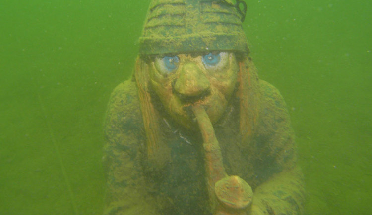 Garden gnome with pipe in its mouth, underwater