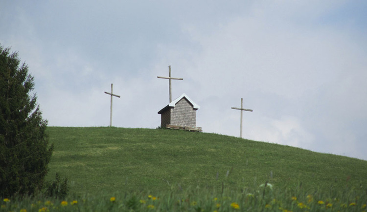 Kreuze und kleine Kapelle auf einem Hügel, im Vordergrund Wiesen