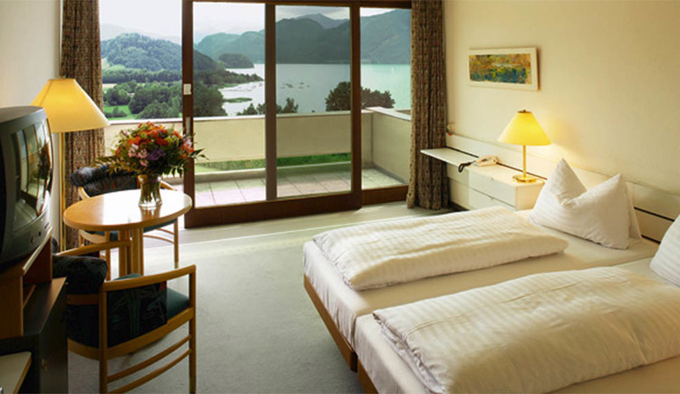 Room with double bed, table lamp, telephone, a table with chairs, TV, in the background a large balcony door with a view of the lake and the countryside