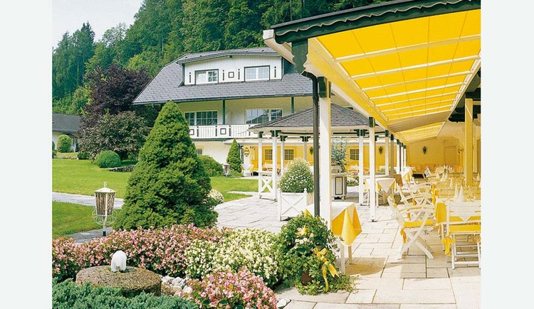 View of the terrace with tables and chairs under an awning, side garden with flowering shrubs, trees, house. (© Hotel Seehof)