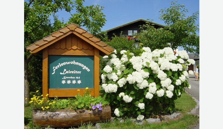 "Sign made out of wood, that says: ""Ferienwohnungen Laireiter, Keuschen 164\"" and has four Edelweiss on it. In front flowers."