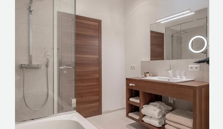 Badezimmer mit Badewanne, Dusche, Bademäntel, Handtücher, Duschtücher in einem Regal, Waschbecken, Spiegel