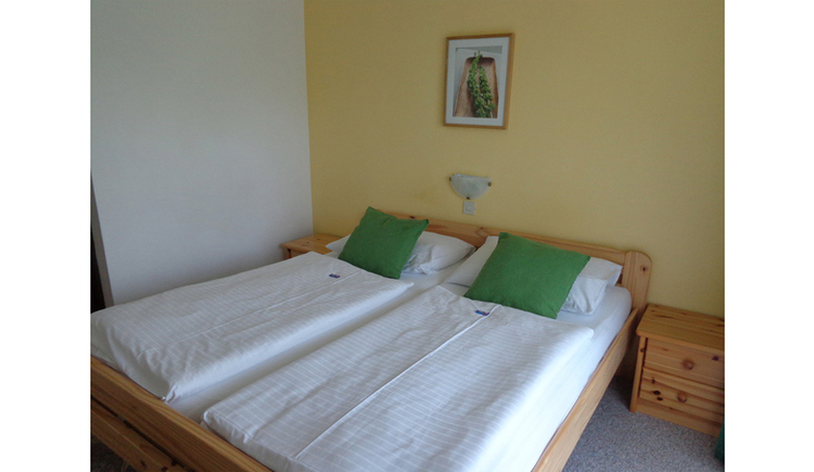 Bedroom with double bed, night-box, picture in background, lamp