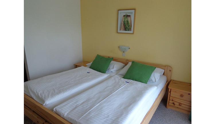 Schlafzimmer mit Doppelbett, Nachtkästchen, Bild im Hintergrund, Lampe