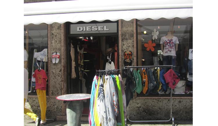 Blick auf das Geschäft, im Vordergrund Kleidung auf den Ständer
