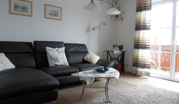 Modern ausgestattetes Wohnzimmer mit gemütlicher Sitzgarnitur und Balkon