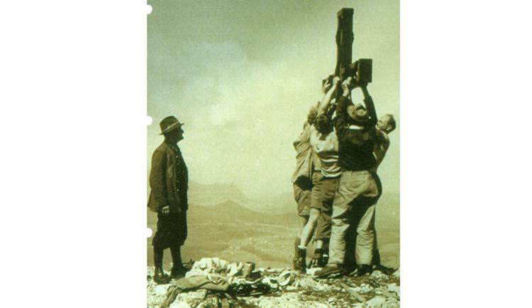 Personen stellen ein Kreuz auf