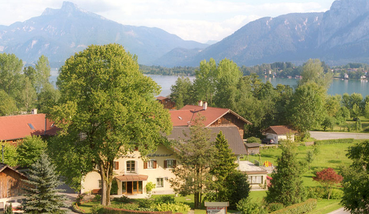 View of the hotel - behind trees, in the background the lake and the mountains