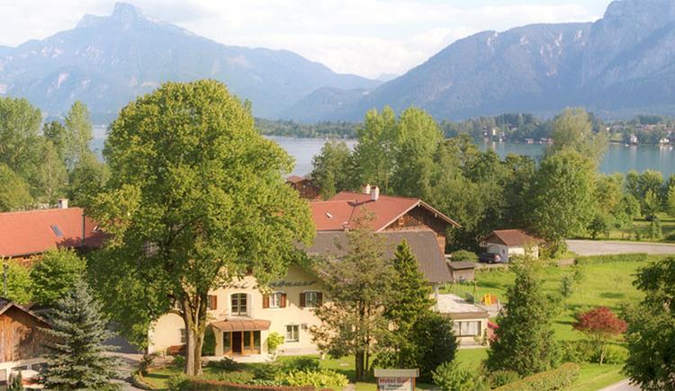 Blick auf das Hotel ein - wenig versteckt hinter Bäumen, im Hintergrund der See und die Berge