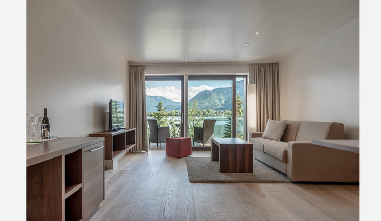 Chest of drawers / table, sideboard with TV, stool, table, couch, in the background view through the large balcony to the terrace with chairs and table, landscape, lake, mountains