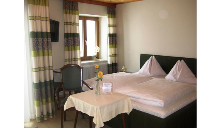 Doppelbett, davor ein Tisch mit einem Stuhl, seitlich ein Fenster