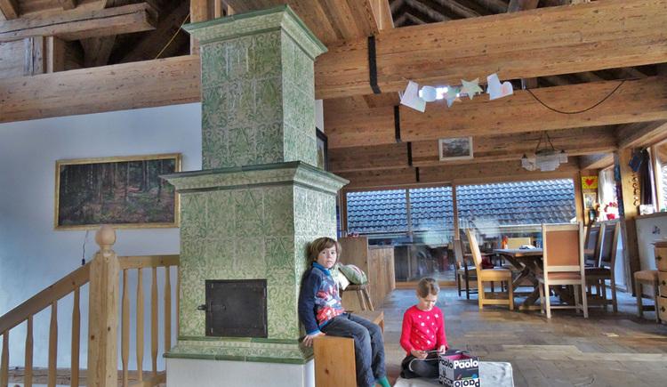 Großer freistehender Kachelofen im Wohnbereich, im Hintergrund Tisch mit Stühlen