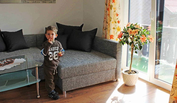 Living area with a big sofa, in front a child