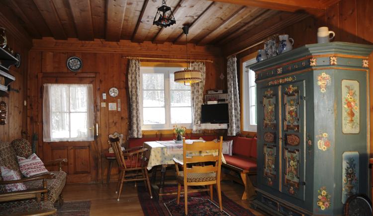Rustikal eingerichtete Stube mit Eckbank, alten Bauernkasten und Sofa