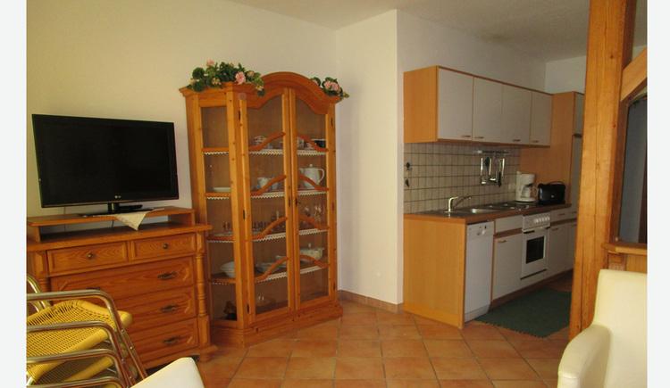 Wohnbereich: im Vordergrund gestapelte Gartensesseln, Holzkommode mit Fernseher, Glasvitrine, im Hintergrund die Küche mit Spüle, Geschirrspüler, Herd, Kaffeemaschine