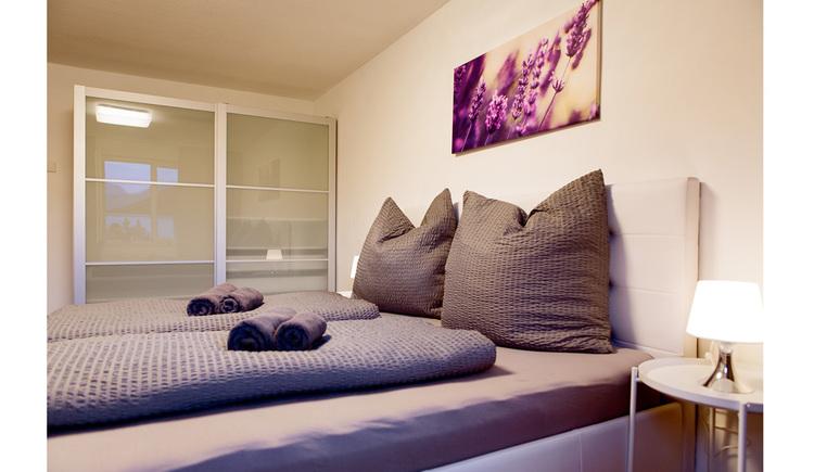 Schlafzimmer mit Doppelbett, seitlich ein kleiner Tisch mit Tischlampe, im Hintergrund ein Schrank