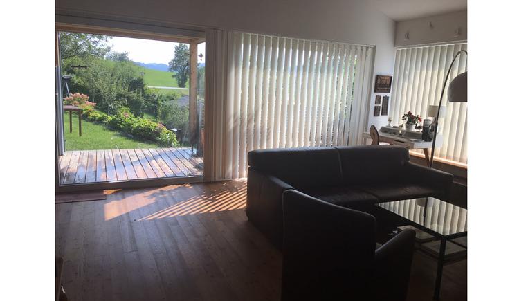 Wohnbereich mit Couch, Tisch, Blick durch die geöffnete große Terrassentür in den Garten