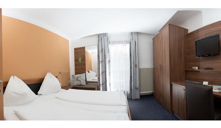 Schlafzimmer mit Doppelbett, seitlich ein Kleiderschrank, Kommode, Fernseher an der Wand, im Hintergrund eine Balkontür