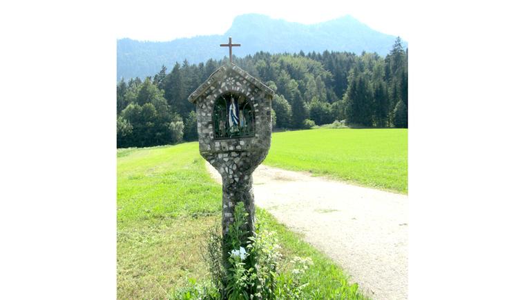 Blick auf ein Steinmarterl mit Madonnafiguren in einer Wiese, seitlich eine Straße, im Hintergrund ein Wald