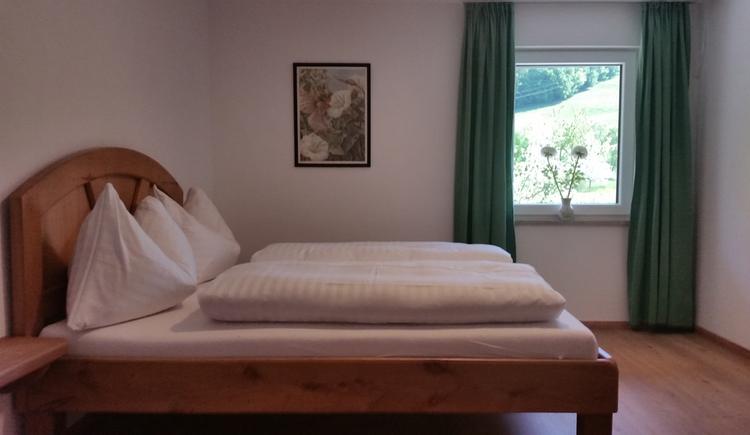 Doppelbett, im Hintergrund ein Fenster, Bild an der Wand