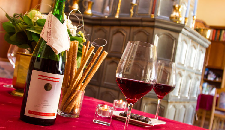 gedeckter Tisch mit Gläser und Wein, Knabbergebäck, Blumen, seitlich im Hintergrund ein Kachelofen