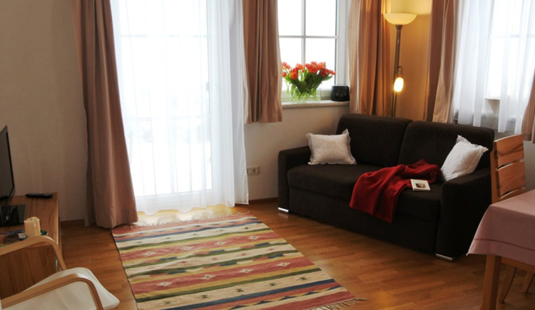 living area with couch, cushions, blanket, TV on a small chest of drawers, balcony door and windows in the background