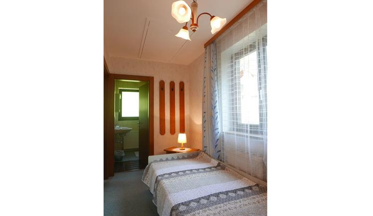 Einzelbett, Nachtkästchen mit Tischlampe, seitlich ein Fenster, Blick durch die offene Tür ins Badezimmer