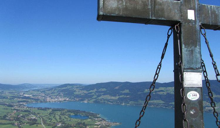 Blick über die Seen und Berge, im Vordergrund ist ein Teil des Gipfelkreuzes zu sehen. (© www.mondsee.at)