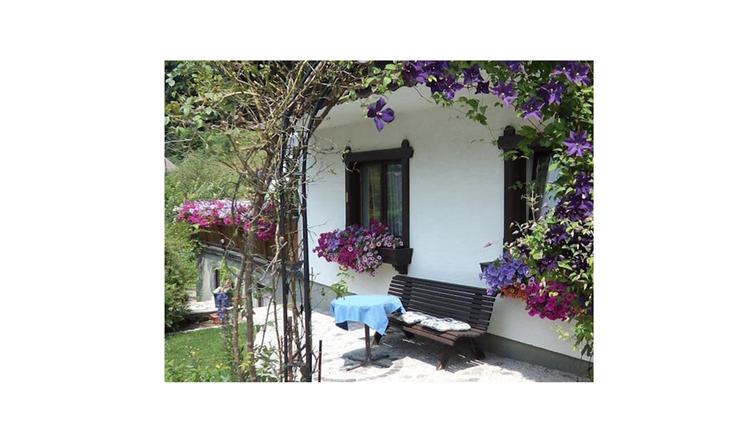 Blick auf das Haus von der Seite, vor dem Haus Gartenbank und kleiner Tisch, Blumen