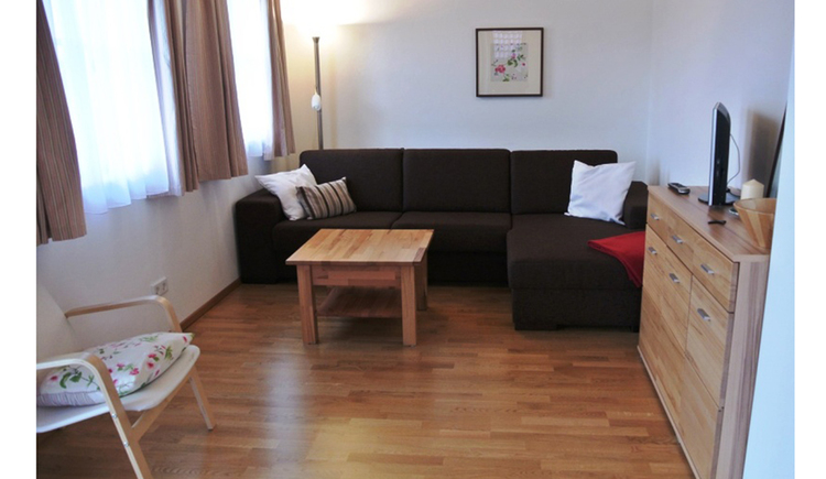 living area with couch ang table, TV on the chest of drawers, window and chair on the side