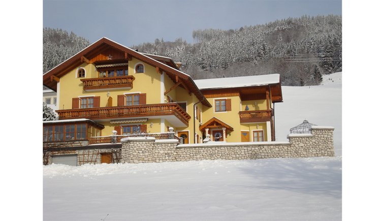 View of the house with balcony, in front and background snowy landscape, trees