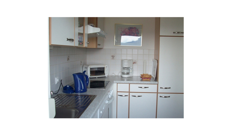 Kitchen with water cooker, stove, microwave, coffee machine