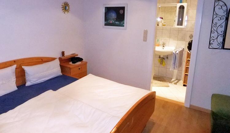 Zimmer mit Doppelbett und Blick in ein offenes Badezimmer
