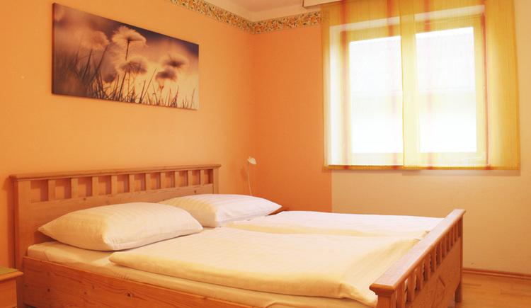 Doppelbett aus Holz vor organger Wand
