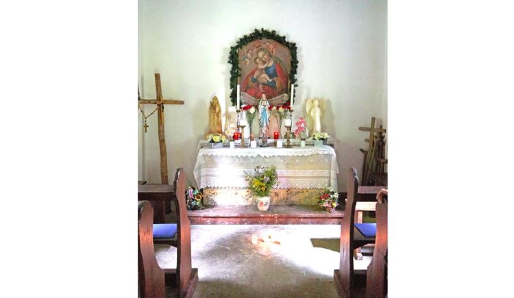Blick auf den Altar mit Kerzen, Heiligen Figur, Heiligenbild, Kreuz, seitlich Holzbänke