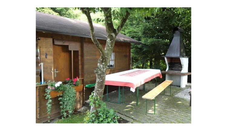 Gartenhütte aus Holz, Bierbänke und Biertisch, im Hintergrund ein Griller