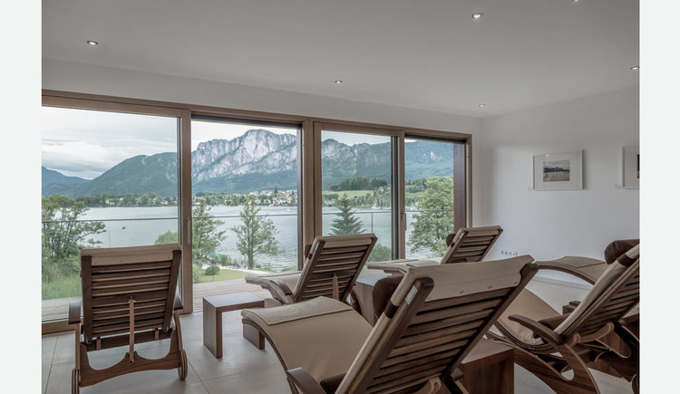 Lounges and small tables, look through the large window fronts to the lake and the mountains