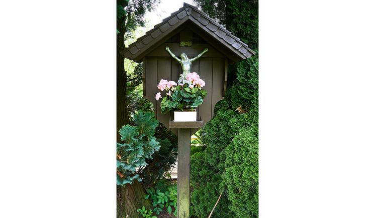Blick auf das Holzwegkreuz, Blumen, im Hintergrund Bäume