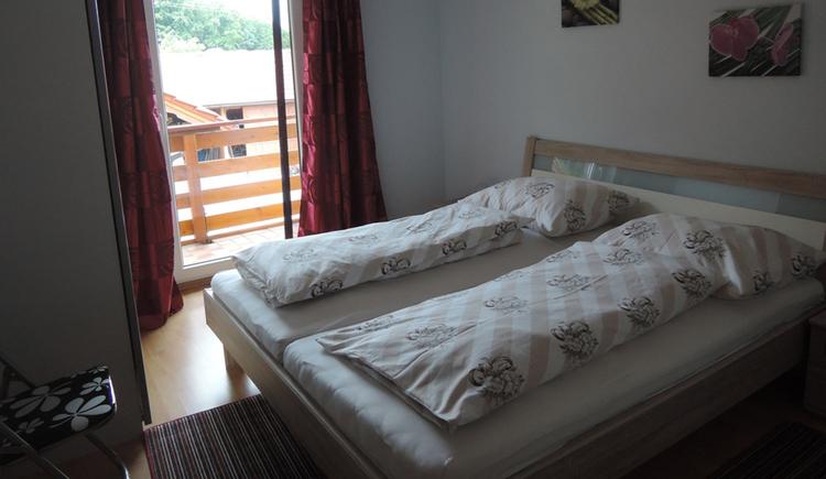 Schlafzimmer mit Doppelbett, seitlich ein Klappsessel