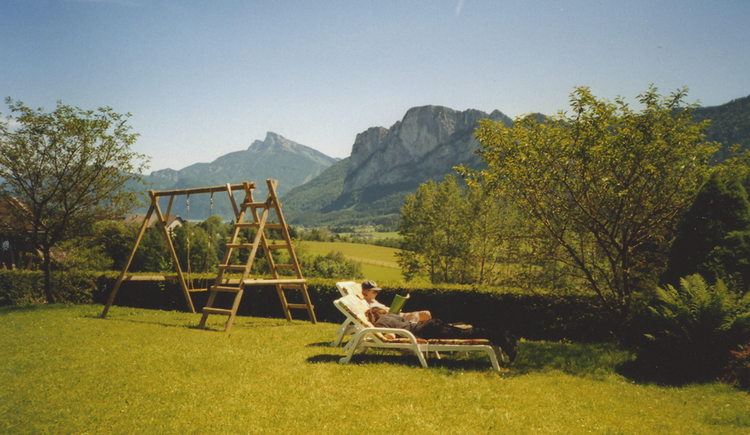 Person in a deck chair in the garden, in the background trees and mountains