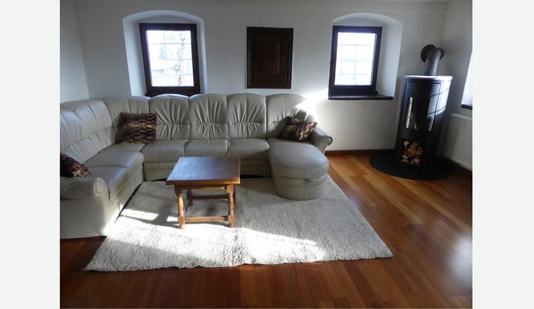 Wohnbereich mit Couch, Tisch, Schwedenofen, im Hintergrund Fenster