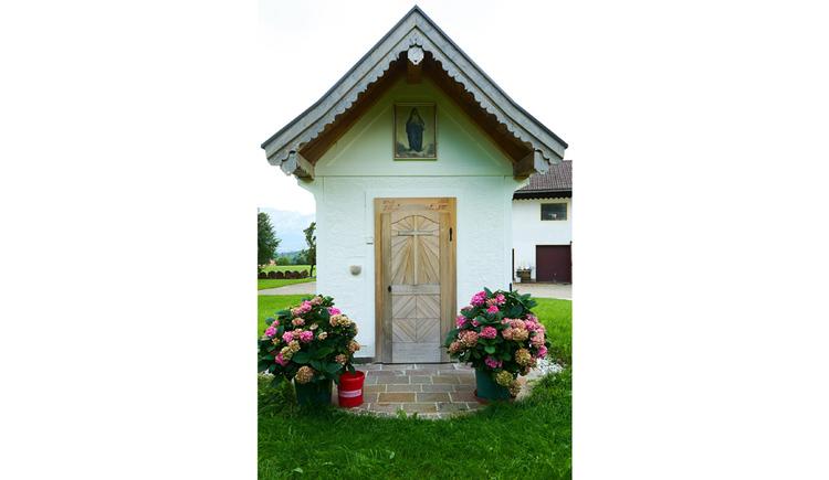 Blick auf die Kapelle, seitlich Blumenstöcke