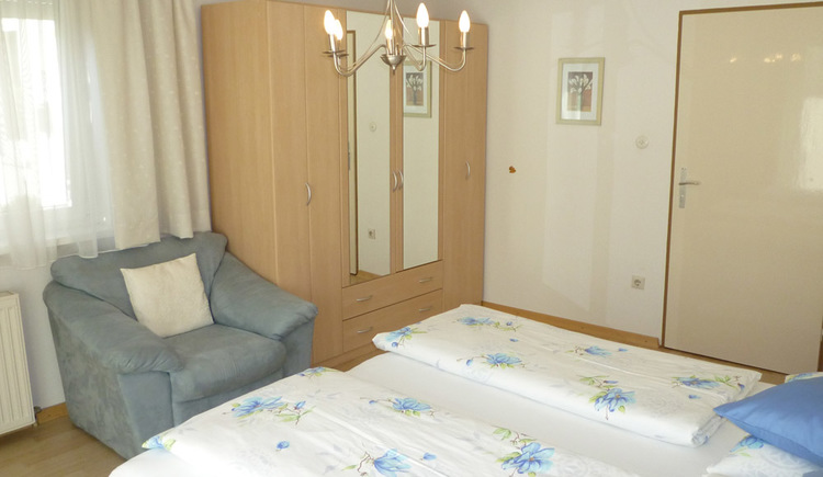 Large, brightly furnished bedroom with double bed and wardrobe