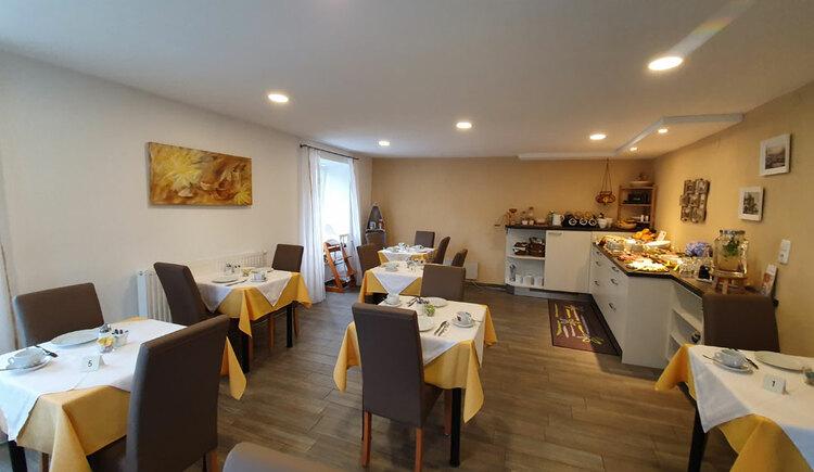 Frühstücksraum, gedeckte Tische an der Seite ein reichhaltiges Frühstücksbuffet. (© Hemetsberger)