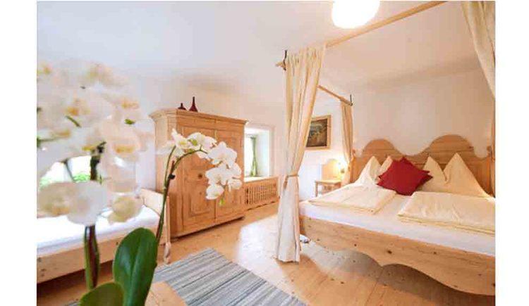 Schlafzimmer mit Himmelbett, im Hintergrund ein Einzelbett, Kasten, Kommode und Fenster, im Vordergrund eine Orchidee