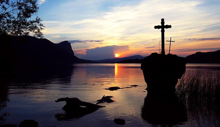 Ein Sonnenuntergangsbild. Rechts das Denkmal Kreuzstein - ein Feldblock im See mit zwei Kreuzen darauf, in der Mitte die rote, untergehende Sonne, links die Silhouette der Drachenwand.
